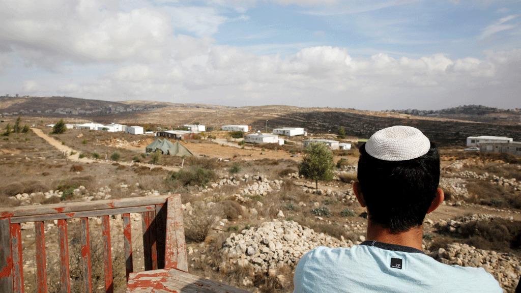 شاب إسرائيلي يقف على نقطة مراقبة تطل على موقع استيطاني يهودي من عمونا في الضفة الغربية