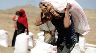 أحد العمال يحمل كيسا من القمح لتوزيعه على النازحين في مخيم بضواحي صنعاء، اليمن (01 مارس 2021)