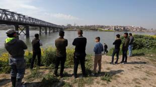 شباب يقفون بالقرب من نهر دجلة