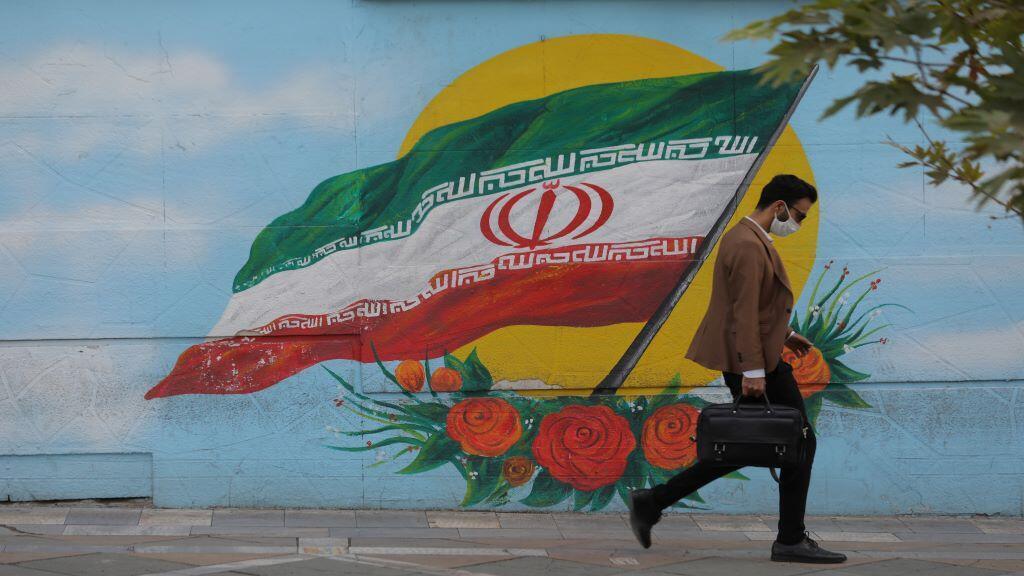 إيراني يضع الكمامة في الطريق العام