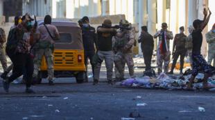 أحد أفراد قوات الأمن العراقية يوجه سلاحه نحو المتظاهرين خلال الاحتجاجات المستمرة المناهضة للحكومة في بغداد-
