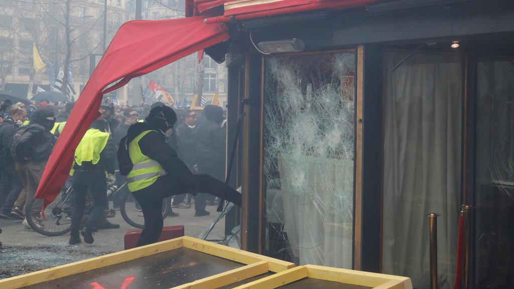 متظاهر بصدد تكسير واجهة محل في باريس يوم 16/03/2019