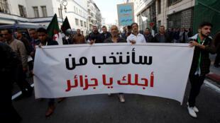 صورة لمحتجين جزائرين يحملون لافتات تؤيد إجراء الانتخابات الرئاسية -