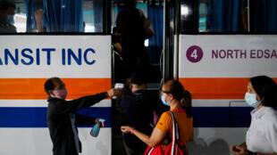 فحص درجات الحرارة لدى الركاب قبل الصعود إلى الحافلة في العاصمة مانيلا