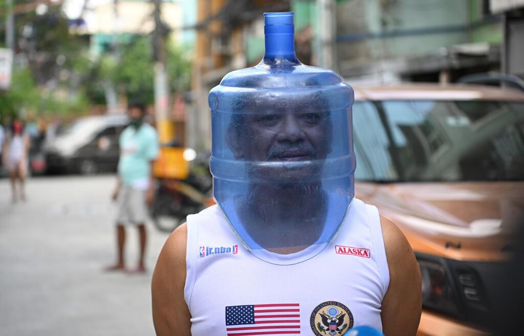 رجل يستخدم خزان مياه بلاستيكي لحماية وجهه في مدينة مانيلا