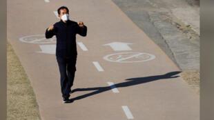 رجل يضع قناعًا يسير في مُنْتزَه في كوريا الجنوبية/