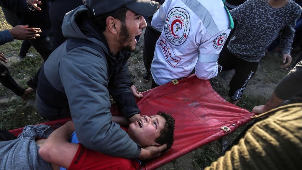 رجل فلسطيني يحمل شابًا مصابًا عند السياج الحدودي مع إسرائيل شرق مدينة غزة في 22 مارس 2019.