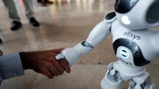 موظف يصافح روبوت خلال مؤتمر في سانتياغو