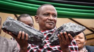 عامل المنجم التنزاني يحمل الحجرين في يديه