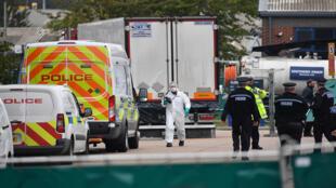 ضباط الشرطة البريطانيون الذين يرتدون بدلات جنائية يعملون في شاحنة أثناء عملهم شرق لندن ،بعد العثور على 39 جثة في حافلة في 23 أكتوبر 2019
