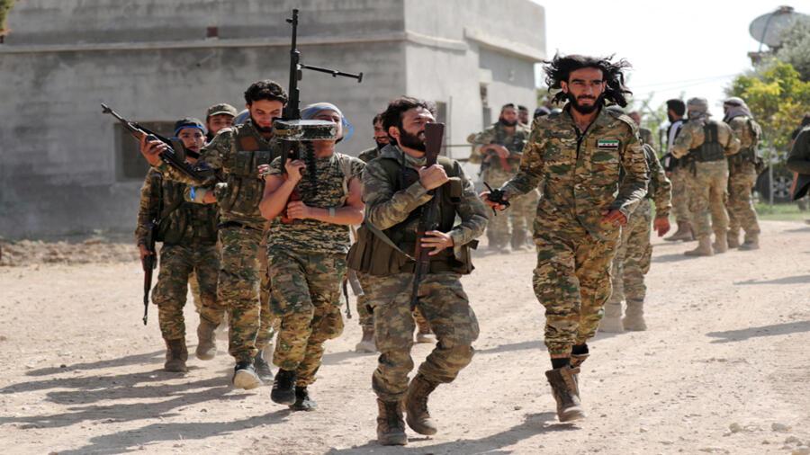 سوريون مدعومون من تركيا يسيرون معًا في سوريا
