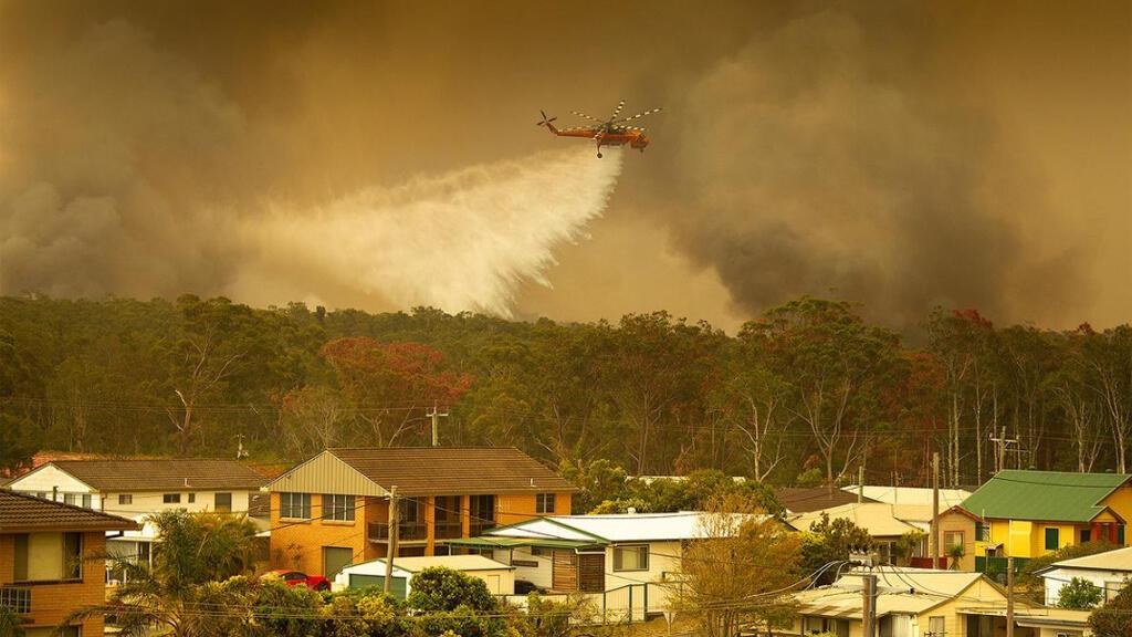 طائرة تحاول إخماد الحرائق المستعرة في هارينجتون في أستراليا