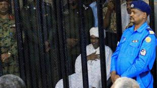 الرئيس السوداني السابق عمر حسن البشير يجلس في حراسة داخل قفص في المحكمة حيث يواجه تهما بالفساد ، في الخرطوم-