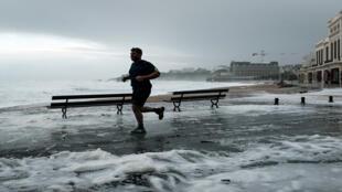 رجل يركض على البحر في شاطئ بياريتز الكبير في جنوب غرب فرنسا في 3 نوفمبر 2019 خلال عاصفة اميلي