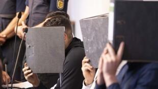 صورة التقطت يوم 26 يونيو 2019، لثلاثة من المتهمين بالاغتصاب وهم يخفون وجوههم خلف المجلدات عند بدء محاكمتهم في محكمة للقاصرين في فرايبورغ جنوب ألمانيا