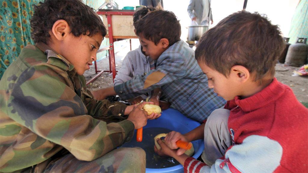 أطفال يشاركون بتحضير الغداء في مدرسة  بصنعاء 17 مايو/أيار 2015
