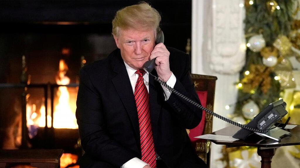 الرئيس الأمريكي دونالد ترامب يتلقى اتصالات تليفونية من أطفال يتصلون بقيادة الدفاع الجوي بأمريكا الشمالية لتعقب حركة بابا نويل في البيت الأبيض بواشنطن