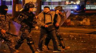رجال الشرطة يلقون القبض على متظاهر لبناني