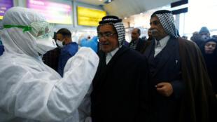 فريق طبي عراقي يفحص درجة حرارة الركاب ، وسط تفشي فيروس كورونا الجديد ، لدى وصولهم إلى مطار النجف-