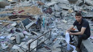 شاب فلسطيني يجلس وسط حطام منزله بعد هجوم صاروخي اسرائيلي
