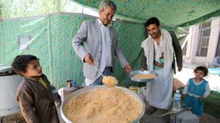 رجل يوزع الغذاء على النازحين في مدرسة بصنعاء 17 مايو 2015