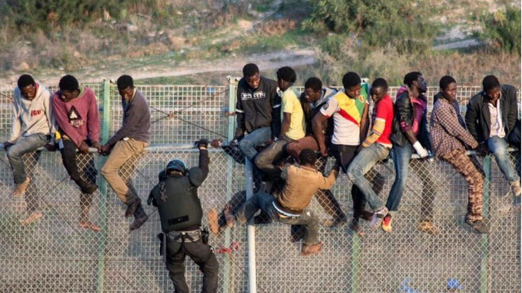 مهاجرون يتسلقون السياج الحدودي بين سبتة والمغرب 2015