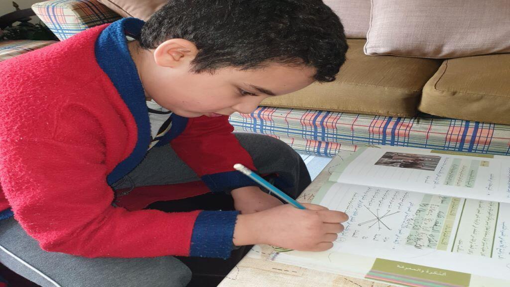 تلميذ في الصفوف الابتدائية يراجع دروسه في البيت، لبنان