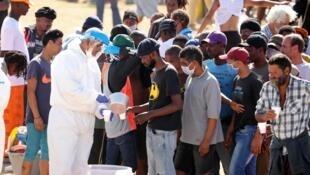 أشخاص يتلقون المساعدات والأغذية من السلطات المحلية، في ظل الحظر المفروض لمكافحة وباء كورونا، جنوب إفريقيا