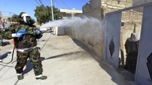 عضو في الدفاع المدني العراقي يطهر حيًا في مدينة النجف يوم 3 مارس / آذار 2020