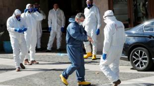 عمال يرتدون ملابس واقية يستعدون لتعقيم مبنى إقليمي لاحتواء تفشي فيروس كورونا