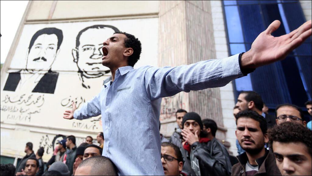 متظاهرون يرددون شعارات مناهضة للعسكر ووزارة الداخلية أمام نقابة الصحافيين في القاهرة في 25 يناير 2015