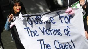متظاهرة ضد الانتهاكات الجنسية التي ارتكبها رجال دين