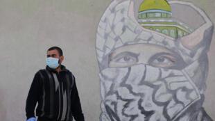 رجل من غزة يرتدي قناعا ويقف أمام جدارية