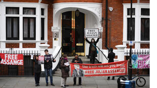 يعرض أنصار مؤسس ويكيليكس جوليان أسانج لافتات ولوحات إعلانية وهم يجتمعون خارج السفارة الإكوادورية في لندن في 5 أبريل 2019 ، في أعقاب شائعات بأن أسانج على وشك الطرد.