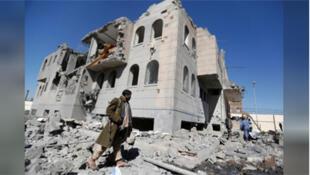 مسلح من الحوثيين بالقرب من مبنى تعرض لدمار بفعل ضربات جوية
