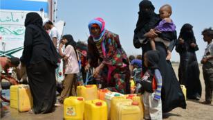 نساء وأطفال ينتظرون للتزود بالماء في منطقة حديدة القريبة من البحر الأحمر 15-02-2016