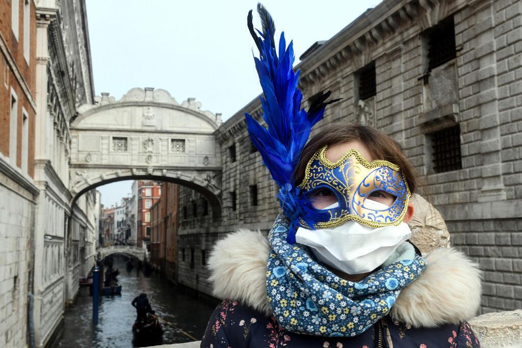 سائحة شابة يرتدي قناع كرنفالياً للوقاية من كورونا في شوارع البندقية