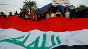 المتظاهرون العراقيون يحملون العلم العراقي خلال الاحتجاجات المستمرة المناهضة للحكومة ، في بغداد-