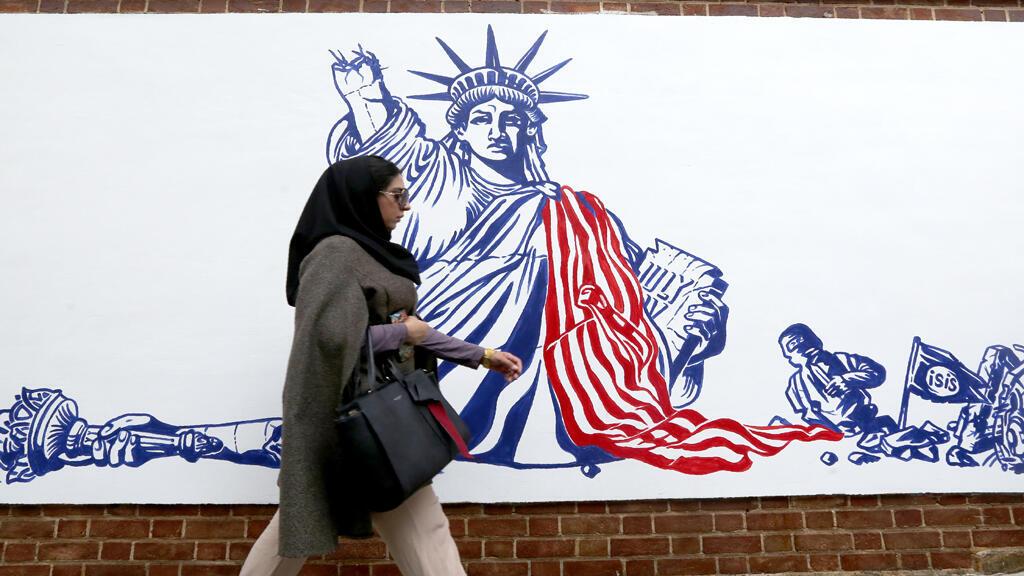 ايرانية تمر أمام رسم جداري على واجهة مقر السفارة الأمريكية السابقة في طهران في 2 تشرين الثاني/نوفمبر 2019