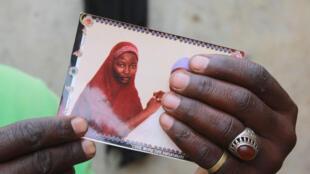 موسى ماينا تحمل صورة ابنتها المخطوفة حوا في شيبوك، شمال غرب نيجيريا