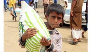 تظهر هذه الصورة التي التقطت في 15 أغسطس 2018 يمنيين نازحين من الحديدة يتلقون مساعدات غذائية من منظمة غير حكومية يابانية في مقاطعة عبس الشمالية في محافظة حجة.