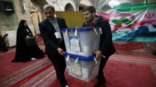 رجلان يحملان صندوقي انتخابات إيران البرلمانية