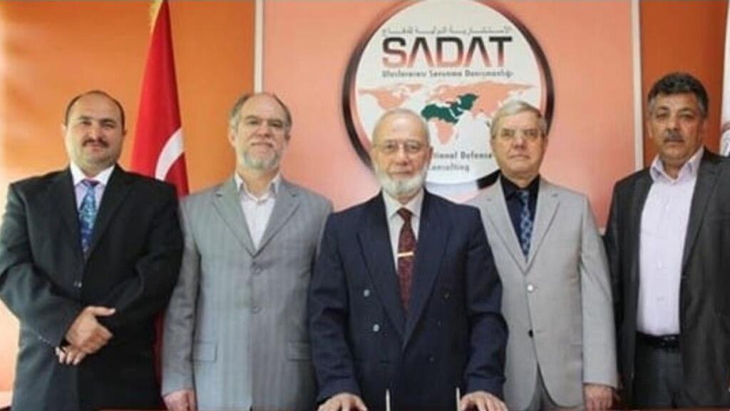 """مؤسس شركة """"سادات"""" عدنان تانري فردي يتوسط مجموعة من المسؤولين بالشركة"""