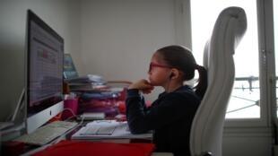 أناييس، وهو تلميذة في إحدى المدارس الباريسية، تتلقى دروسها في غرفتها في المنزل بعد إغلاق المدارس التي فرضها تفشي وباء كورونا، باريس