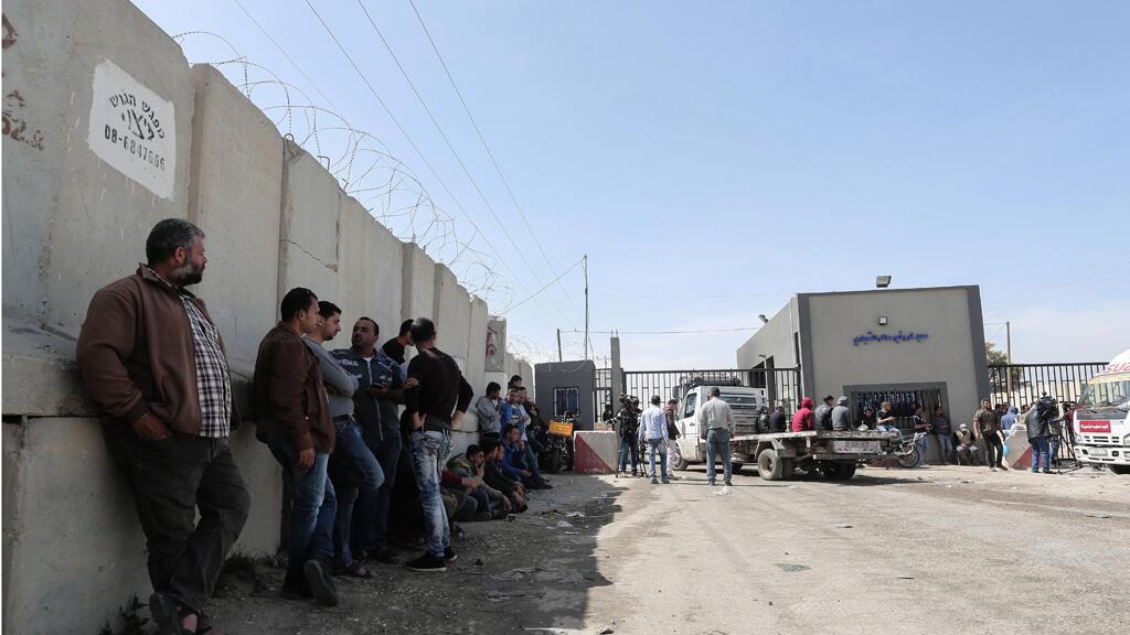 سائقي الشاحنات الفلسطينيين يجلسون مع شاحناتهم بالقرب من معبر كيرم شالوم بين جنوب قطاع غزة وإسرائيل في 22 مارس 2018.