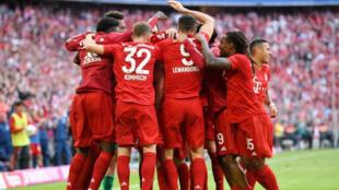 لاعبون من بايرن ميونيخ يحتفلون بتسجيل الهدف الرابع خلال مباراة أمام أينتراخت فرانكفورت في دوري الدرجة الأولى الألماني لكرة القدم يوم السبت