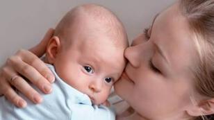 أم تحمل طفلها الرضيع-