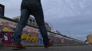 رجل يمشي بجوار جدار برلين