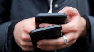 امرأة تحمل هاتفين