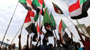 شباب يحملون علم بلادهم السودان